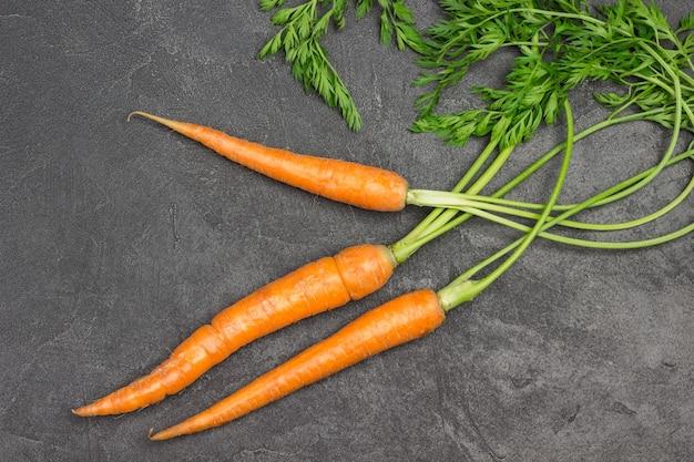 Cenouras frescas com tampos verdes na mesa. fundo preto. postura plana