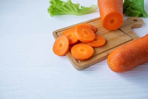 Cenouras frescas cortadas em uma tábua de madeira