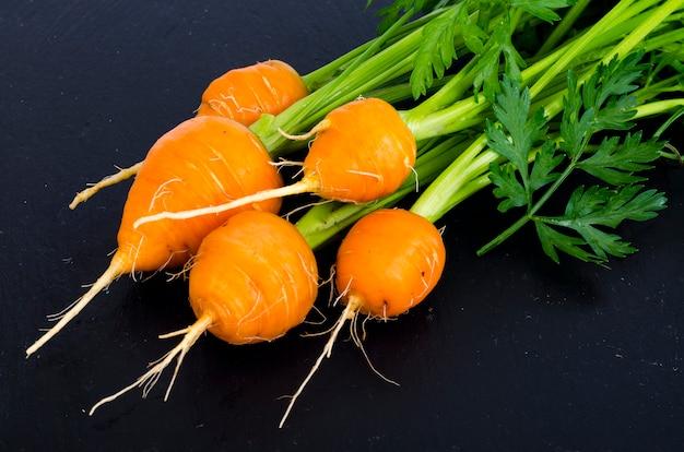 Cenouras frescas do fazendeiro orgânico no fundo preto.