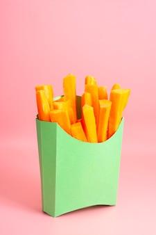 Cenouras frescas em palitos de lanche em uma caixa de papel verde sobre fundo rosa