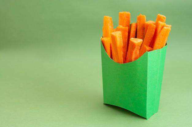 Cenouras frescas em palitos em uma caixa de papel verde sobre fundo verde