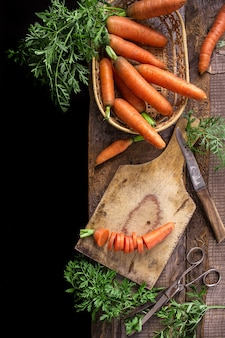 Cenouras frescas na tábua velha, vista superior
