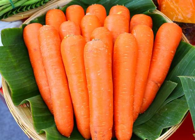Cenouras frescas no cesto contra folha de bananeira