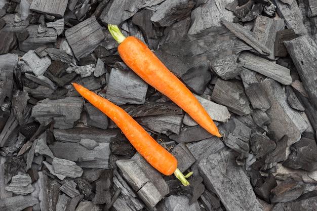 Cenouras jovens inteiras no carvão. alimentos grelhados. nutrição saudável orgânica.