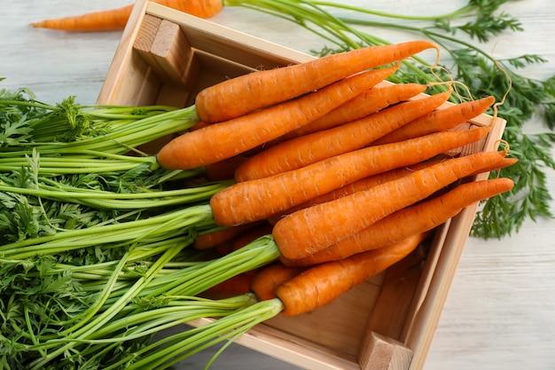 Cenouras maduras e doces em uma caixa na mesa de madeira