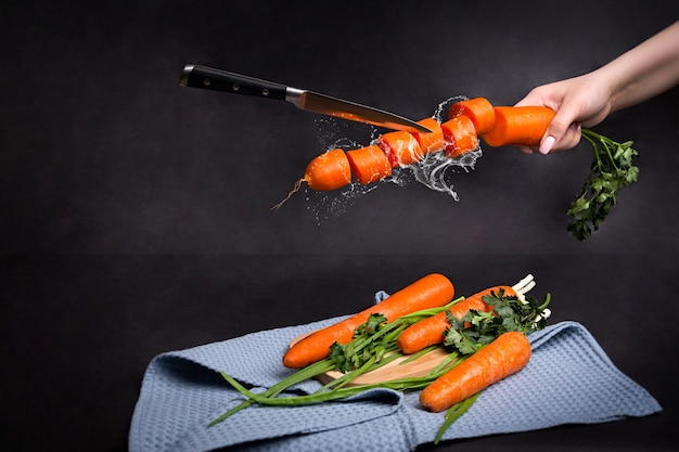 Cenouras maduras inteiras e fatiadas em um fundo preto
