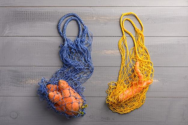 Cenouras naturais feias da moda em dois sacos de barbante ecológicos na superfície de madeira