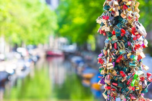 Centenas coloridas de cadeados-bloqueios de amor no canal em amsterdã, holanda