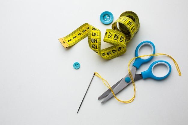 Centímetro de vista superior de costura e tesoura azul