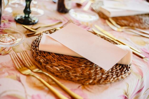 Centrais elegantes com talheres de ouro para um casamento, com um cartão branco vazio