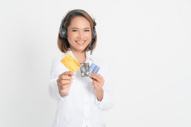 Central de atendimento mulher com fone de ouvido segurando e cartão de crédito.