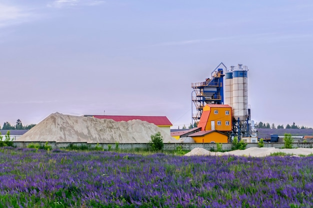 Central dosadora de concreto entre campos floridos no interior