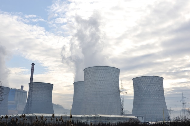 Central elétrica a carvão com torres de resfriamento que liberam vapor na atmosfera