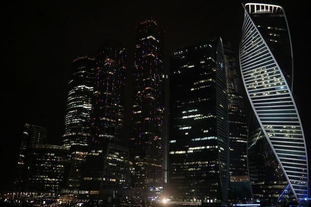 Centro comercial em uma grande cidade com arranha-céus à noite