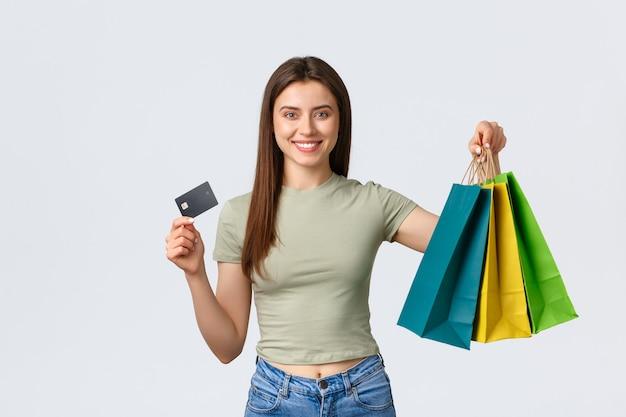 Centro comercial, estilo de vida e conceito de moda. garota animada, comprando roupas novas para as férias de verão, sorrindo e mostrando o cartão de crédito com sacolas de lojas de fom, fundo branco.