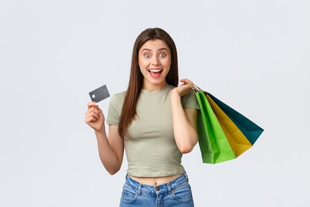 Centro comercial, estilo de vida e conceito de moda. jovem alegre e elegante comprando roupas novas, segurando bolsas e cartão de crédito, sorrindo para a câmera como anunciante de descontos especiais de verão