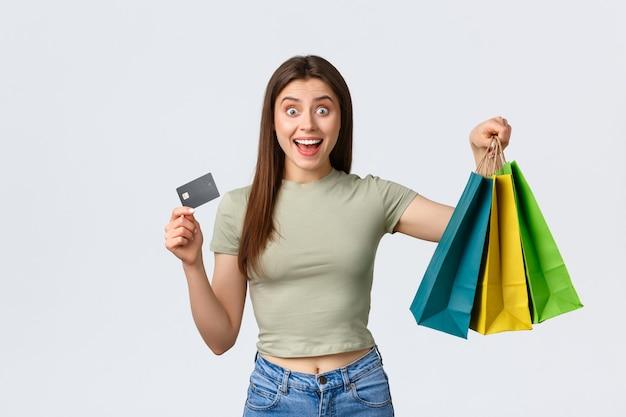 Centro comercial, estilo de vida e conceito de moda. mulher bonita animada compra roupas novas, looks de verão, mostrando cartão de crédito e sacolas com mercadorias, sorrindo maravilhada.