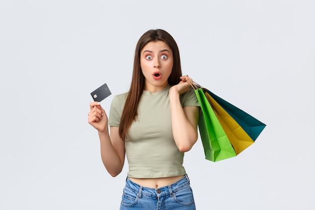 Centro comercial, estilo de vida e conceito de moda. mulher chocada e impressionada com cartão de crédito comprando roupas novas, vendo desconto especial, corre até o caixa com as malas.