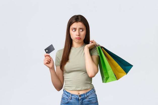 Centro comercial, estilo de vida e conceito de moda. mulher de beicinho fofa sombria e triste reclamando do cartão de crédito vazio, parecendo desapontada segurando sacolas por cima do ombro.