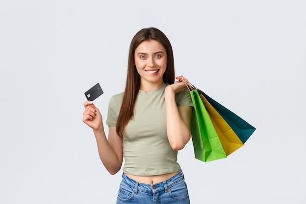 Centro comercial, estilo de vida e conceito de moda. mulher jovem sorridente animada mordendo o lábio, tentação de desperdiçar todo o dinheiro no cartão de crédito, segurando sacolas com roupas e parecendo satisfeito, fundo branco.