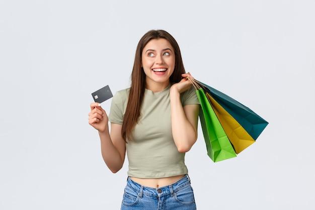 Centro comercial, estilo de vida e conceito de moda. mulher sonhadora, bonita e elegante com cartão de crédito e bolsas de loja, pensando em férias perfeitas com roupas novas que comprou.