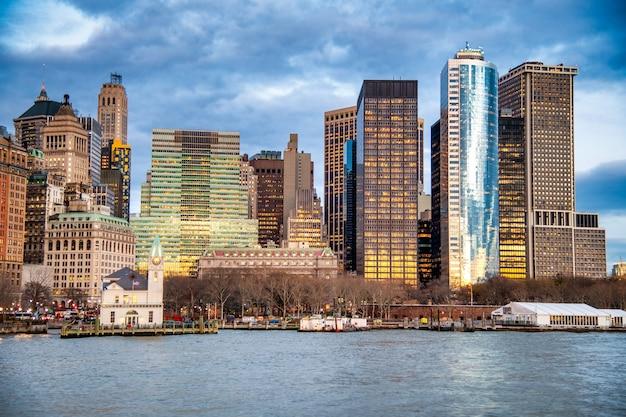 Centro da cidade de nova york ao pôr do sol de uma balsa em movimento.