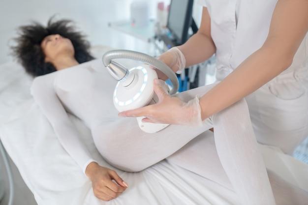 Centro de beleza. mulher jovem sorridente com roupas brancas especiais em procedimento de hardware no centro de beleza e as mãos do médico