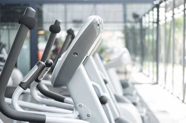 Centro de fitness, interior de academia, health club com equipamento de treinamento esportivo para exercícios aeróbicos e musculação.