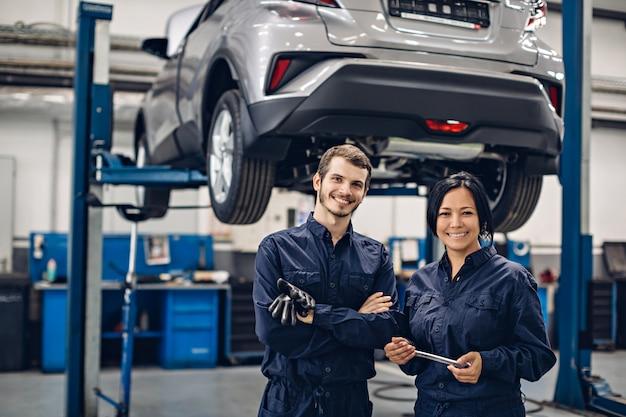 Centro de serviço de reparação automóvel. dois mecânicos felizes - homem e mulher em pé ao lado do carro
