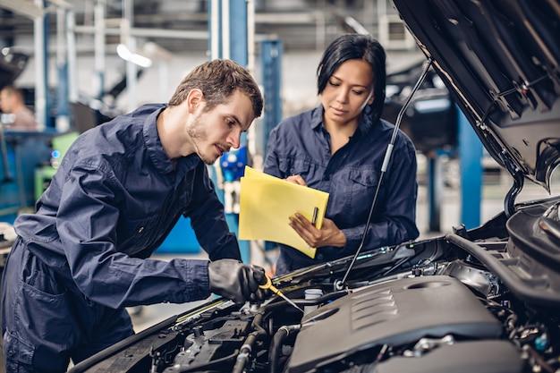 Centro de serviço de reparação automóvel. dois mecânicos - homem e mulher examinando o motor do carro