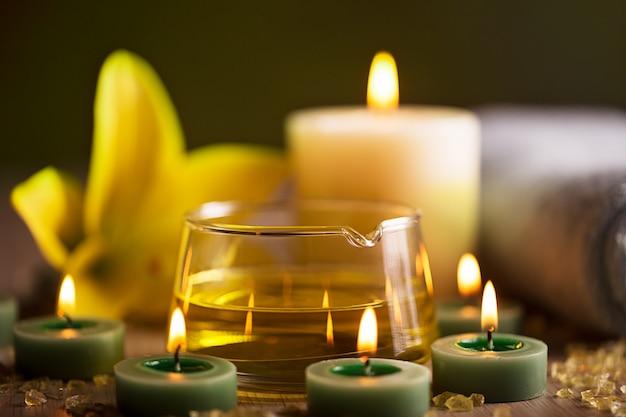 Centro de spa com óleo de ervas, velas e toalha