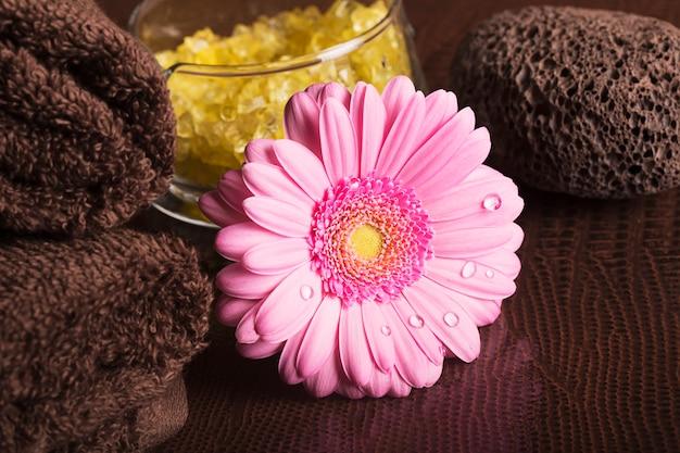 Centro de spa com toalhas e flor gerbera