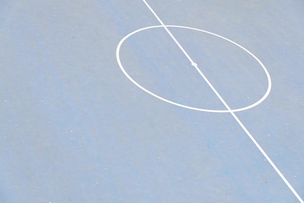 Centro de um campo de futebol do cimento, visto de cima de, com espaço da cópia.