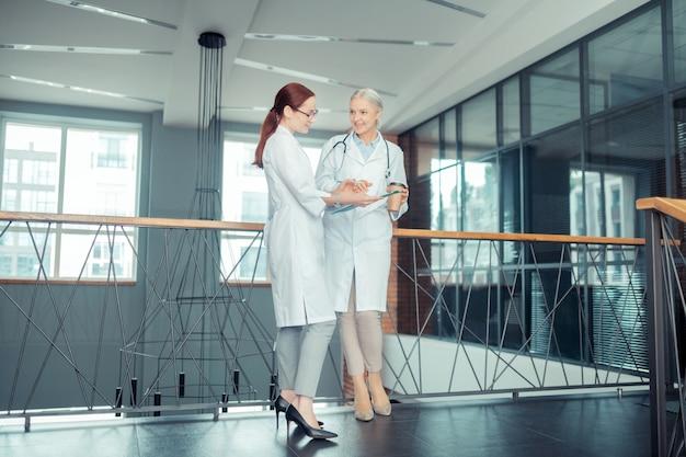 Centro médico. vista lateral de uma jovem médica escrevendo na prancheta ao lado de seu sorridente colega sênior Foto Premium