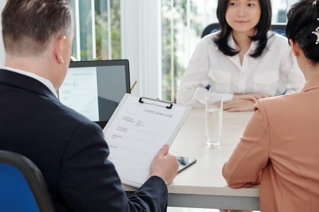 Ceo da empresa ou gerente de recursos humanos olhando para o cv de uma jovem candidata