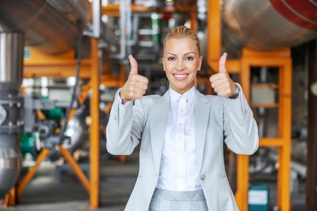 Ceo independente bem-sucedida de meia-idade de terno em pé na usina de aquecimento e mostrando o polegar para cima
