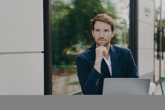 Ceo masculino com expressão atenciosa, navega rápido por internet móvel sem fio em um laptop