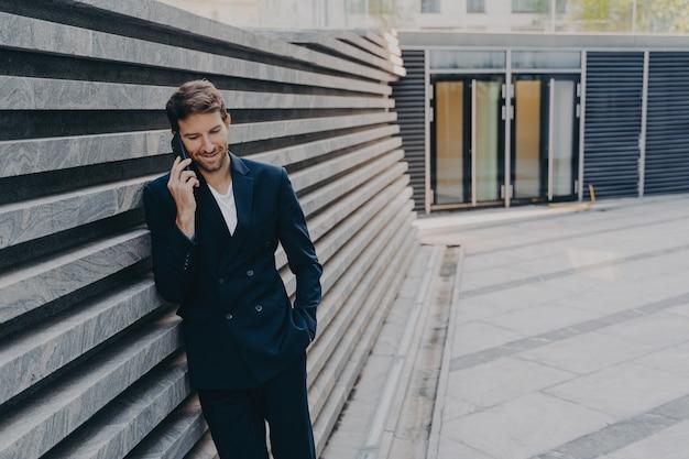 Ceo masculino em uma conversa agradável ao telefone no celular enquanto fica do lado de fora da entrada do centro de escritórios