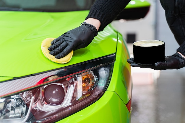 Cera dura para pintura de proteção de automóveis utilizando esponja para remoção de riscos de pintura. aplicação de cera dura com esponja amarela. proteção da pintura.