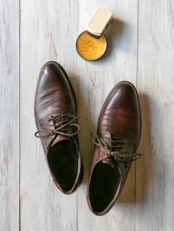 Cera protetora para sapatos de couro. conceito de cuidado de sapato. um par de botas clássicas no chão de madeira.