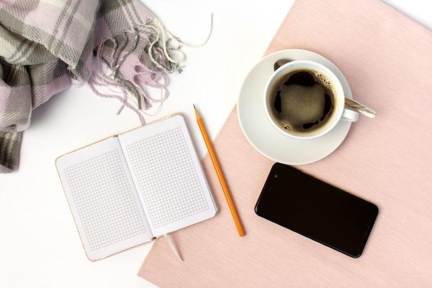 Cerâmica branca xícara de café, caderno, lápis e smartphone na mesa branca