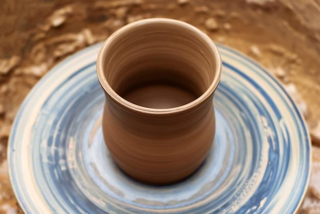 Cerâmica de barro quase concluída em uma roda de oleiro giratória