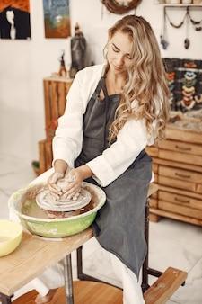 Cerâmica feminina trabalhando com argila na roda em estúdio. barro com água respingou em torno da roda de oleiro.