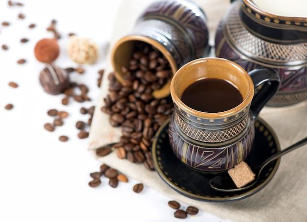 Cerâmica preta velha, grãos de café, balas e um copo de bebida