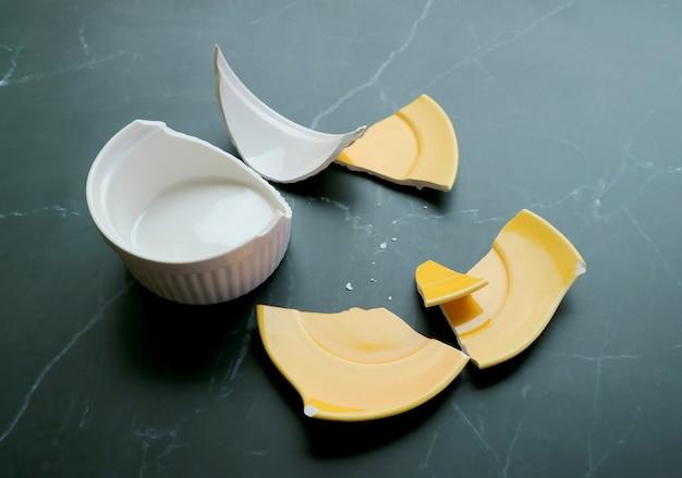 Cerâmica quebrada branca e amarela espalhada no chão preto da cozinha
