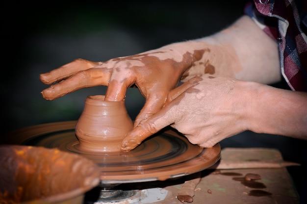 Cerâmica tradicional, close-up das mãos do oleiro moldando uma tigela