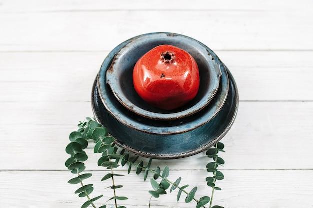 Cerâmica turquesa e romã vermelha