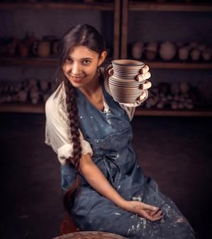 Ceramist girl mostra o produto acabado de argila em um estúdio de arte