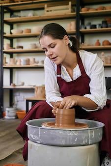 Ceramista artesã trabalha atrás de uma roda de oleiro e esculpe objetos de cerâmica feitos à mão