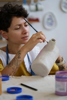 Ceramista profissional pintando cerâmica durante a aula em estúdio para venda em loja de utensílios de cozinha artesanais